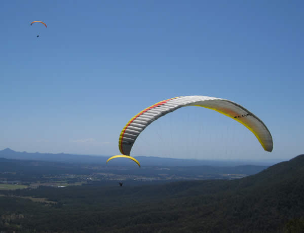 Hang Glider Pilots flying over Canungra with the magnificant view of the Great Dividing Range in the background