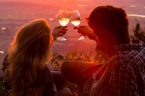 Couple watching the sunset with a glass of wine