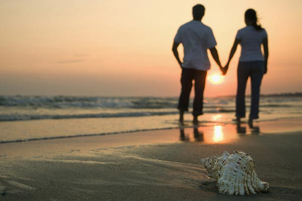Couple walking along Sea Shells on the Beach