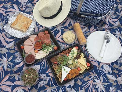 Contents of Picnic Hamper laid out on colourful cloth