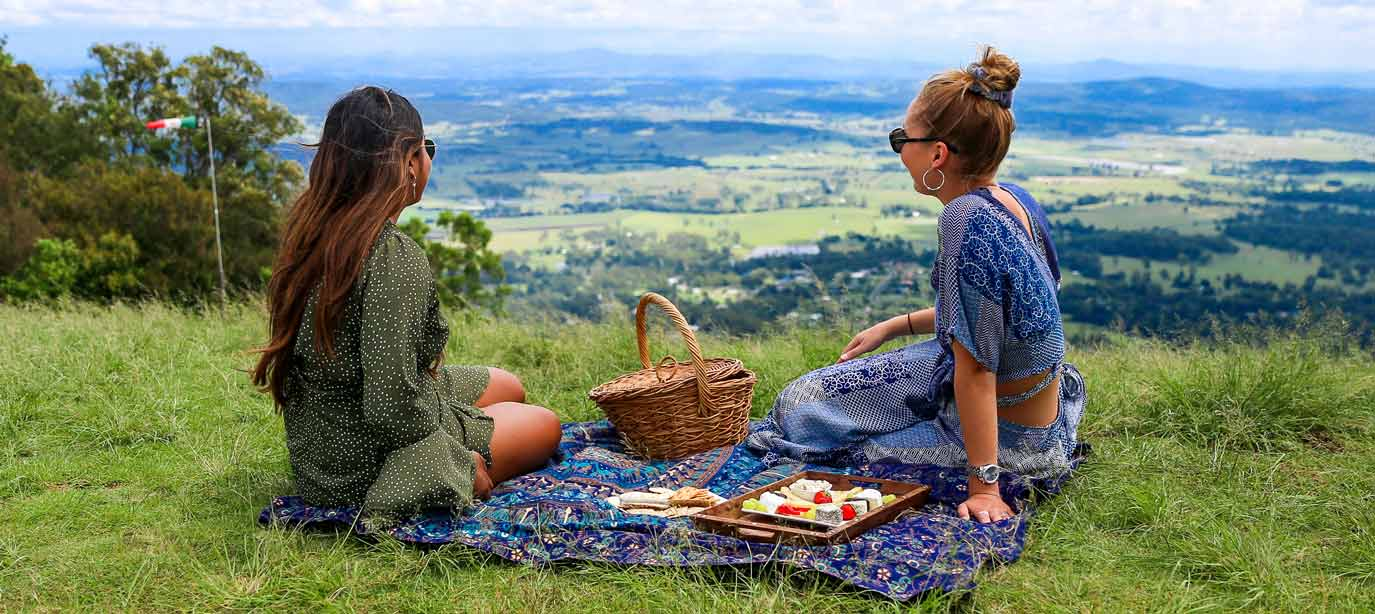 Two women sharing a picnic on Tamborine Mountain