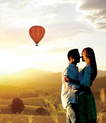 Couple kissing with Hot Air Balloon in background