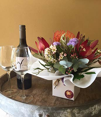 Bunch of flowers and bottle of wine displayed