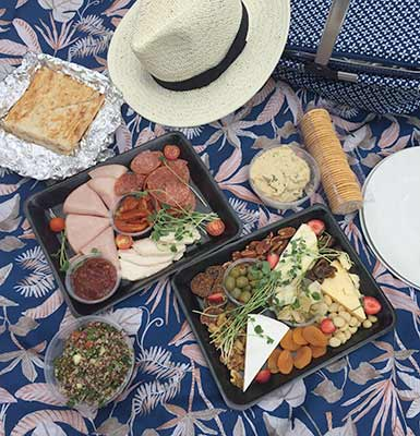 Picnic Hamper spread out on blanket outside