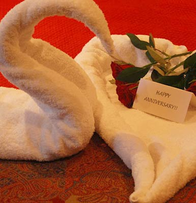 Folded swan towels with flowers and anniversary card