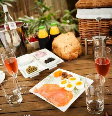 Champagne breakfast hamper laid out on table outside